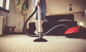 woman cleaning carpet with a vacuum cleaner in room - focus on head of hoover